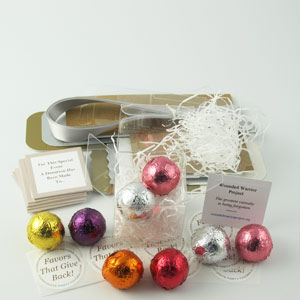 DIY Foil Favors with silver ribbons, clear boxes, white shredding & charity cards - corporate party favors